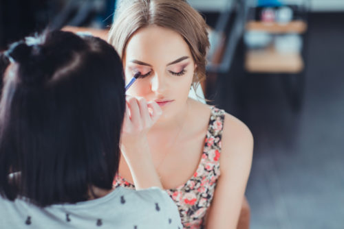 esthetician doing makeup on beautiful young woman