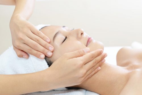 woman getting facial massage from esthetician