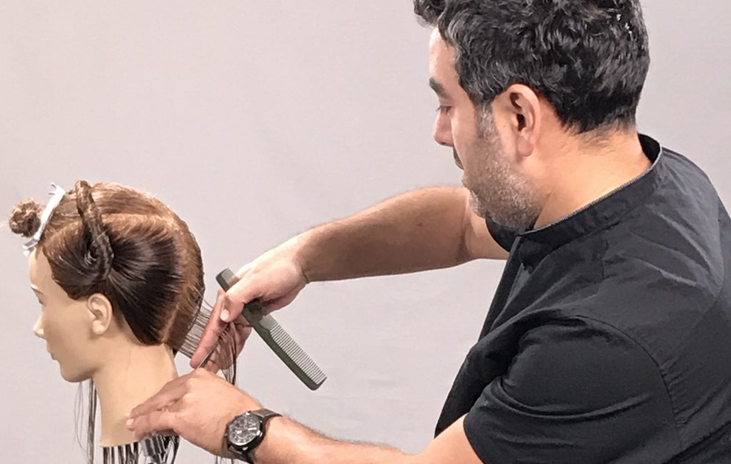 Male hairstylist using left handed scissors to cut hair on mannequin head