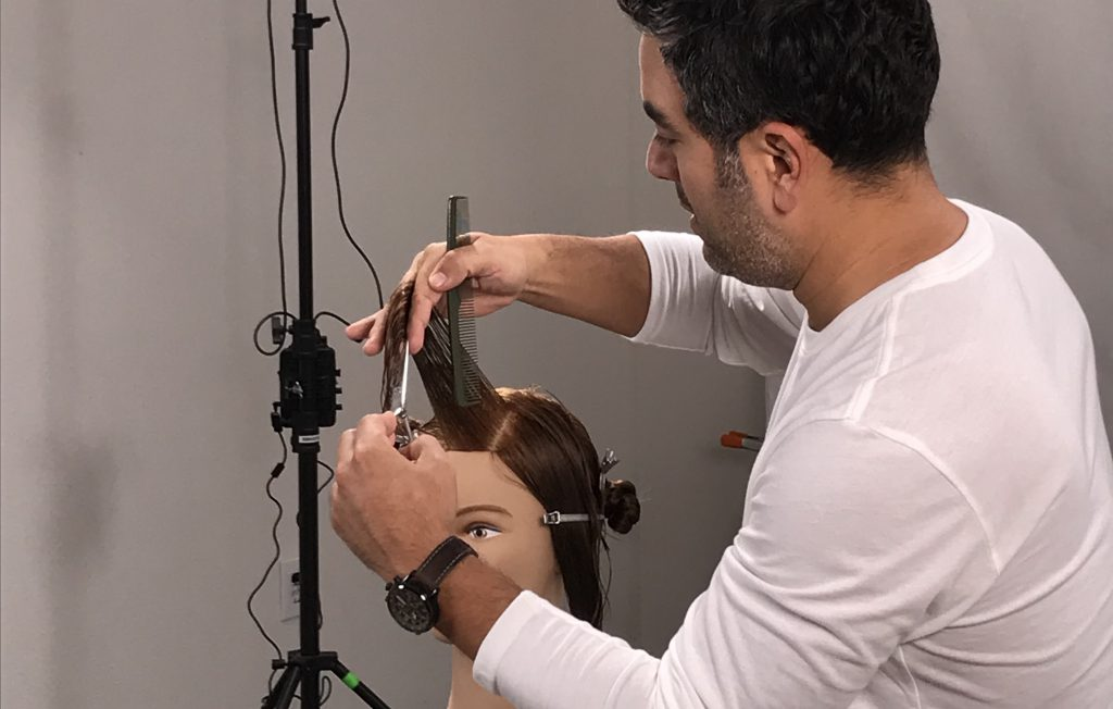 left handed male hairstylist demonstrating how to use left handed scissors on mannequin head