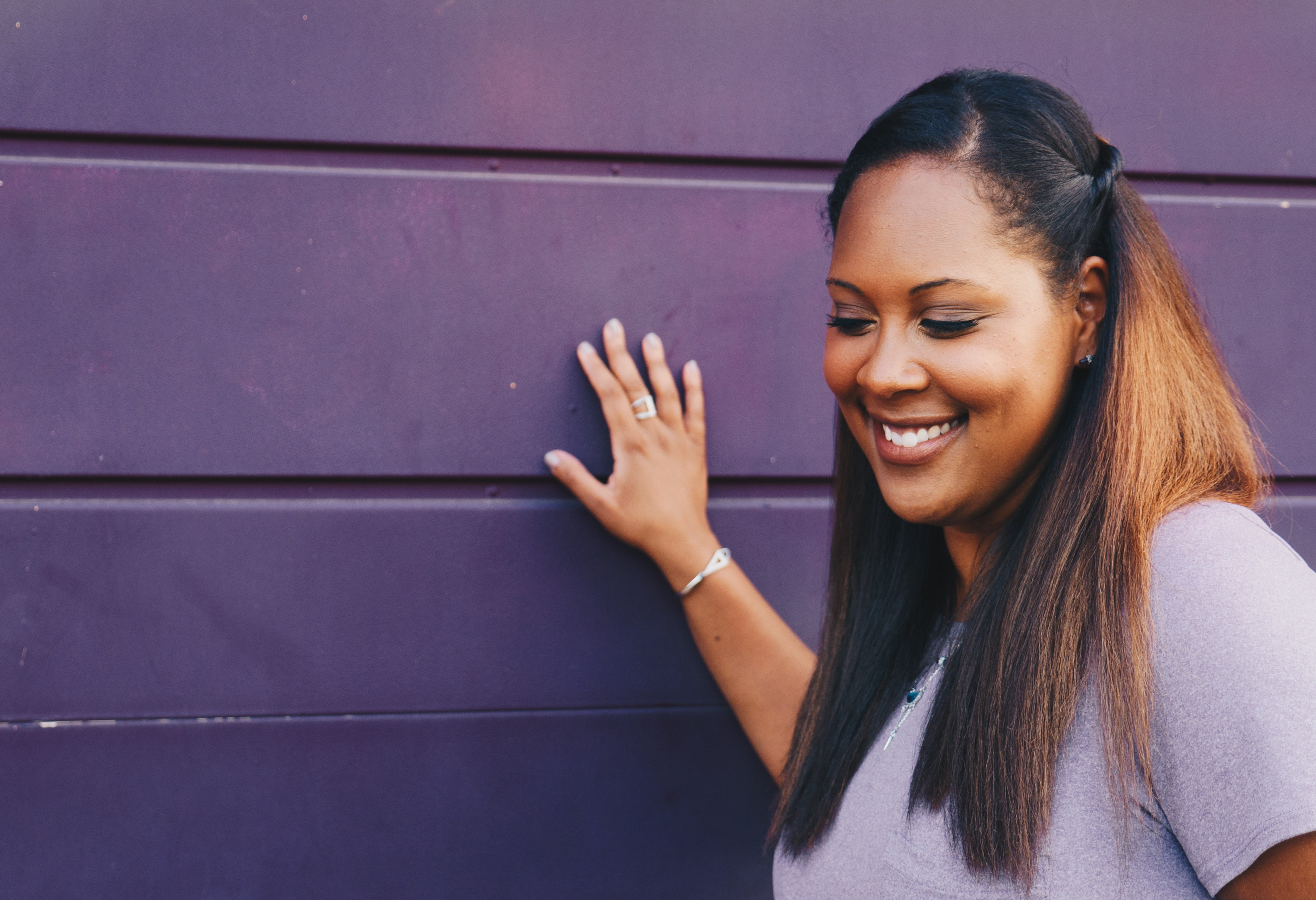 Girl by a purple wall with a simple half-up hairstyle.