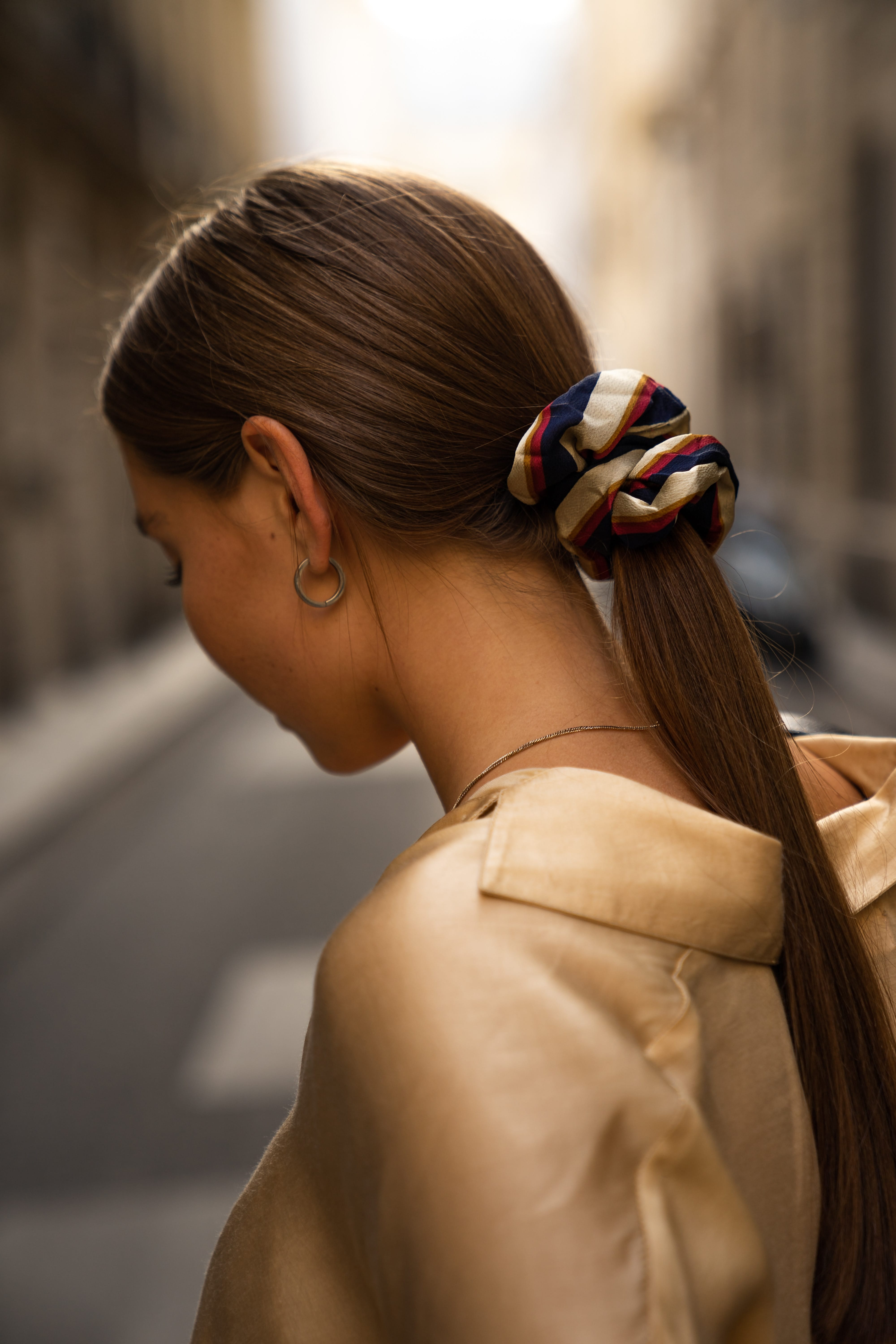 Girl with in a fancy outfit with a low ponytail.