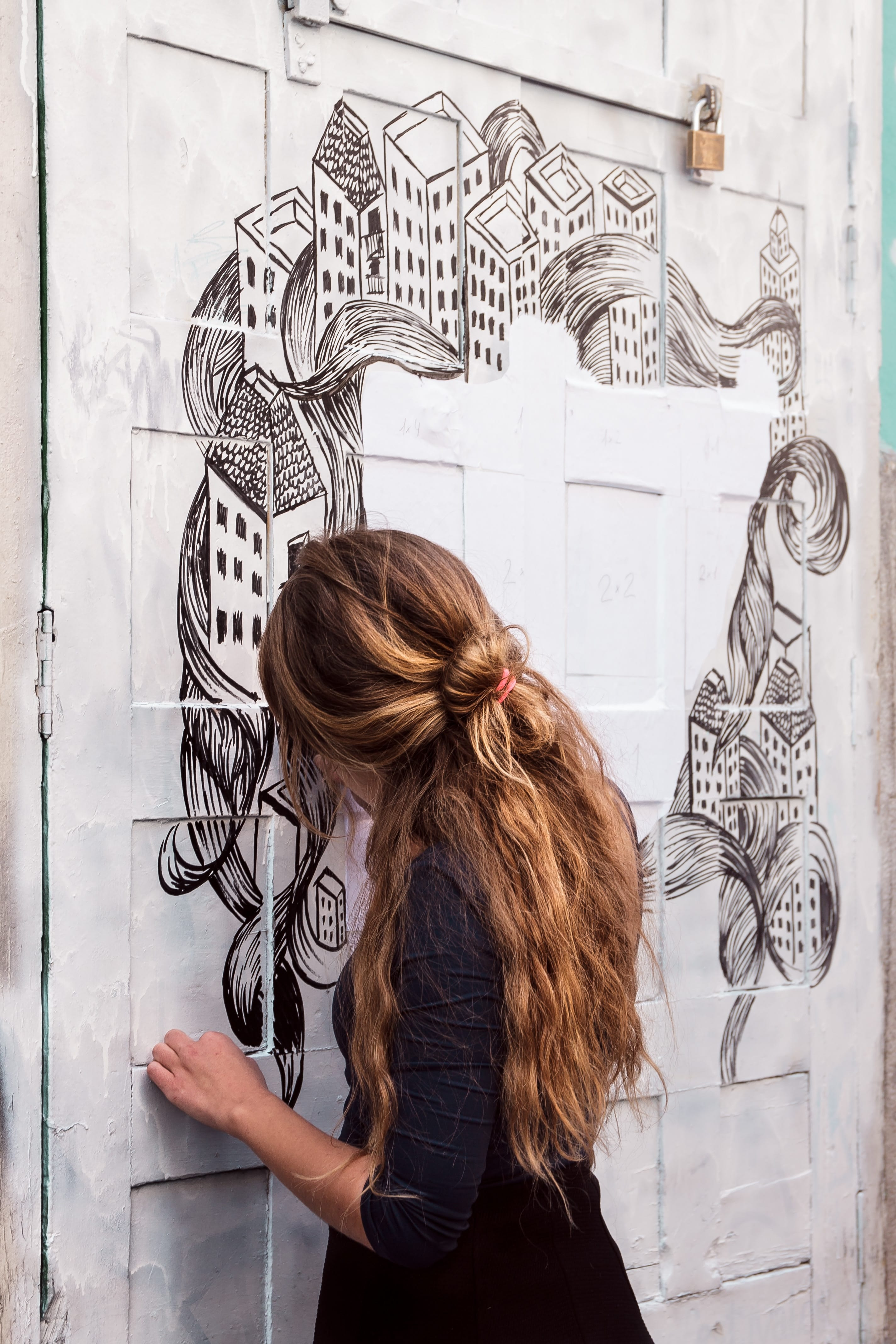 Woman in front of art with long hair in a half-up top-knot.