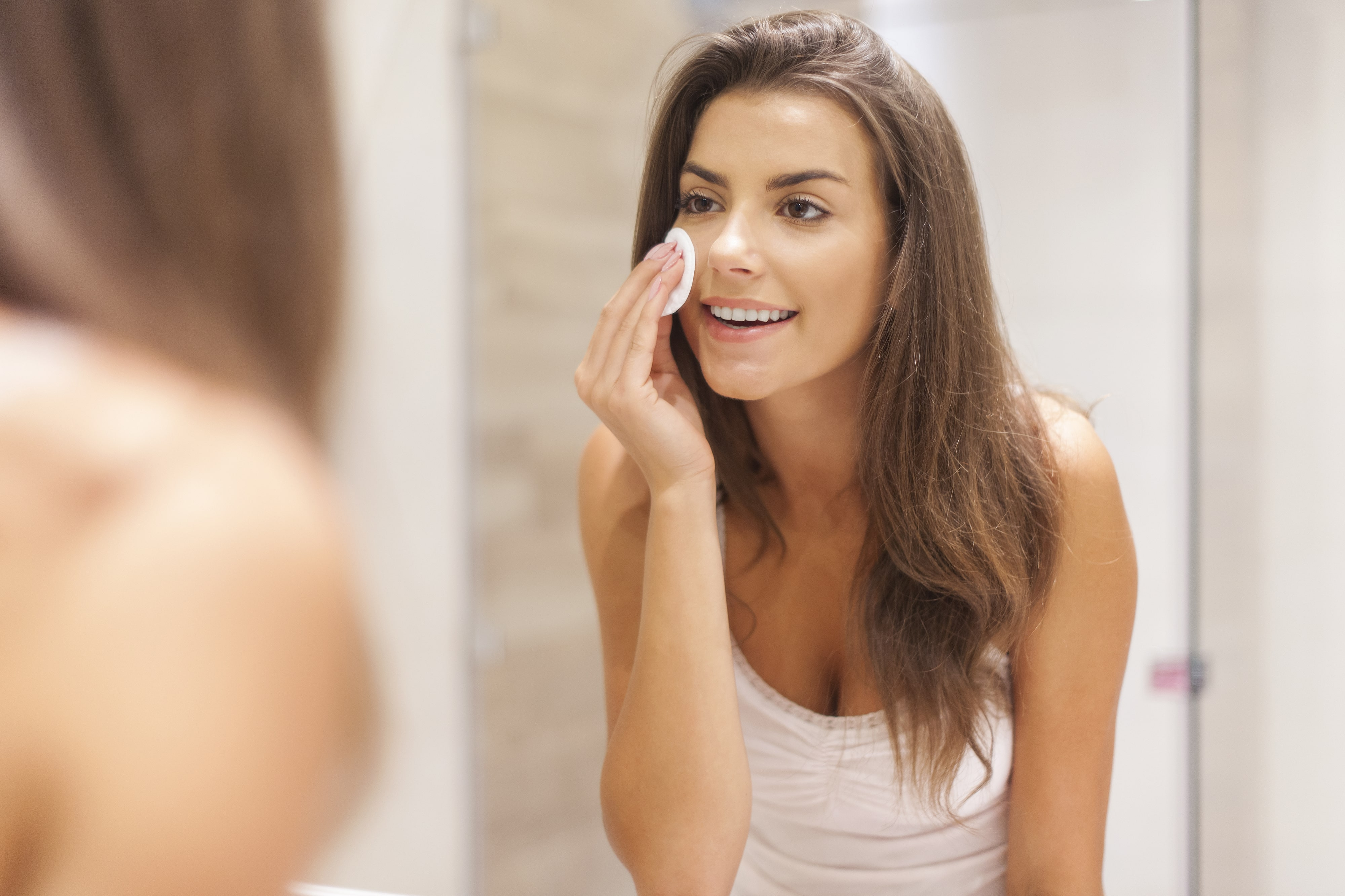 Woman cleaning her face in mirror